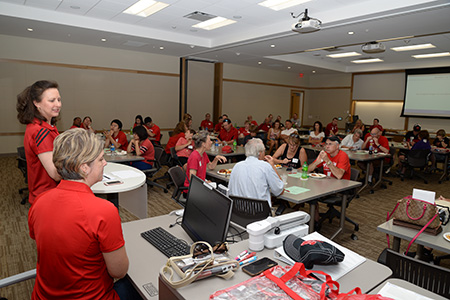 Sue Vagts and Heather Clemens present to actuarial science alumni before a Nebraska football game.