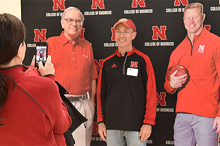 Tailgate attendees posed with fellow alums Warren Buffett and Scott Frost.