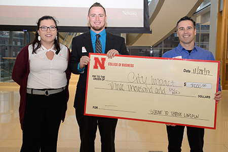 Dustin Schmidt, a senior business administration major from Tekamah, Nebraska, and Burcham present a check to Paige Piper and Christy Pange of the Child Advocacy Center.