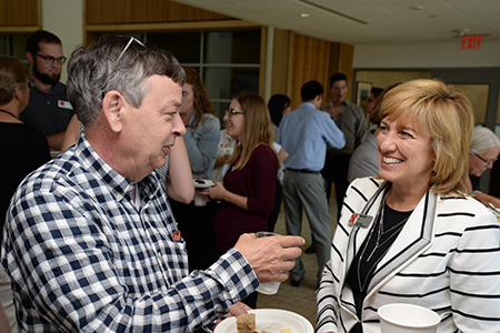 Dr. Matt Cushing, professor of economics, talks with Farrell at one of her Kathy's Point social hours in Howard L. Hawks Hall.