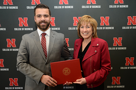 Dr. Kathy Farrell presents Kyle Benesch with his sales certificate during the awards ceremony.