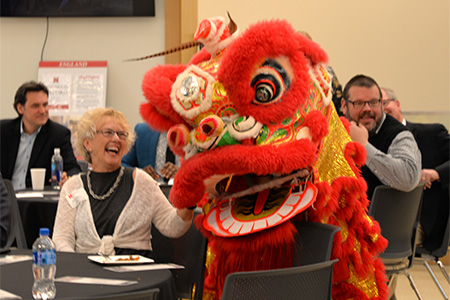 D'vee Buss, assistant dean of undergraduate programs, says 'hello' to one of the lion dancers during the entertainment during the 30th anniversary celebration.