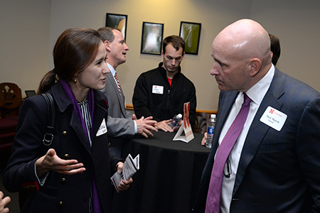 Matt Marsh (right) and the other panelists talk to students at the networking reception following the panel.