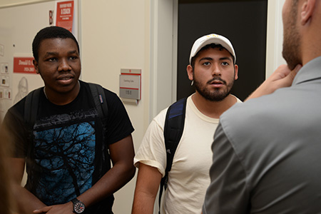 New cohort members Quincey Bernard and Guilber Sorto, Jr., talk to a local entrepreneur in the Clifton Strengths Institute.