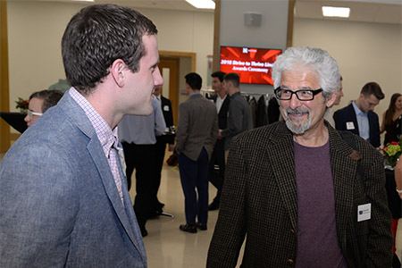 Timothy Wright, a student in the Strive to Thrive Lincoln class project, speaks with Clayton Naff, executive director of Lincoln Literacy, at the awards ceremony reception.