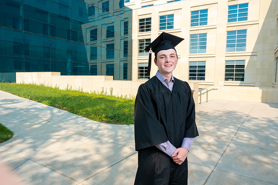 Caleb Newburn in cap and gown standing outside of Howard L. Hawks Hall