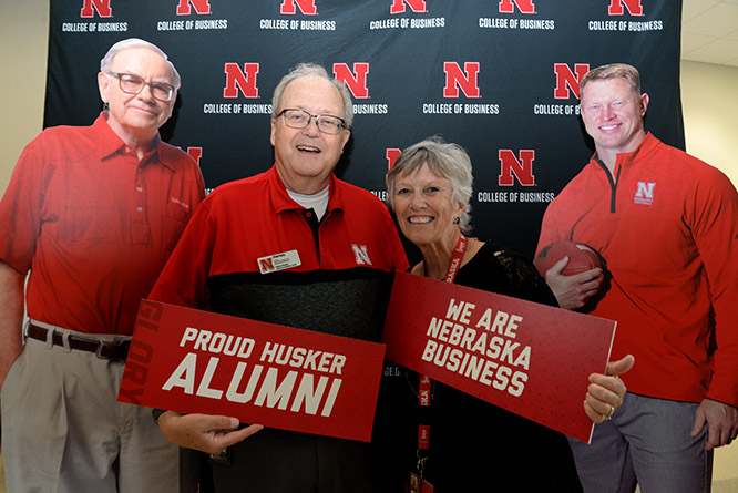 Dr. D'vee Buss, assistant dean of undergraduate programs, poses with Clyde Davis, lecturer of supply chain management and analytics, along with life size cutouts of Buffett and his favorite active football coach Scott Frost at the Back to School Bash.