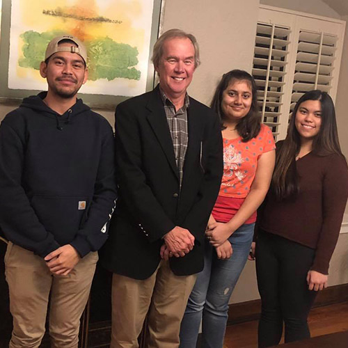 Dr. Dennis Duchon with international students during the Thanksgiving festivities which included some musical interludes on the piano.