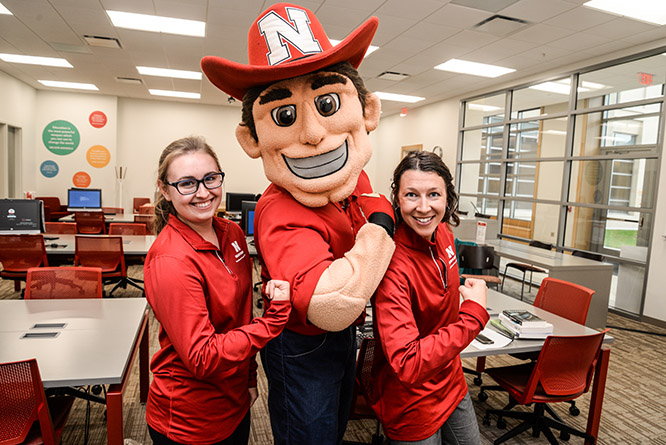 Dr. Kasey Linde poses up with Herbie Husker and Natalie Sneed, a former accounting tutor in the Teaching and Learning Center.