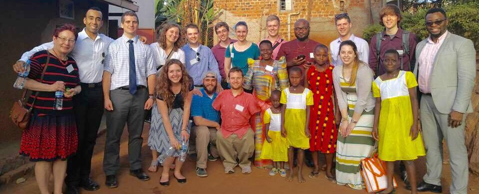 Group shot of Uganda study abroad students, faculty and Madame Benedicta with children